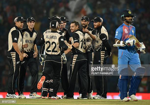 New Zealand bowler Nathan McCullum celebrates with team mates after the wicket of India's batsman Shikhar Dhawan during the World T20 cricket...