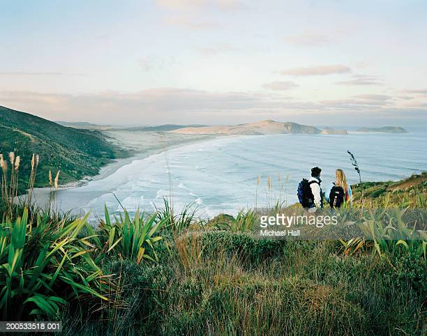 New Zealand, Cape Reinga, couple standing on coast, rear view