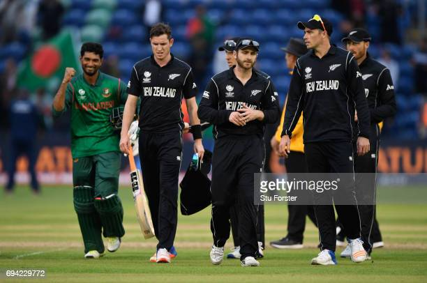 New Zealand captain Kane Williamson leads his team off the field as Bangladesh batsman Mahmudullah celebrates victory after the ICC Champions Trophy...