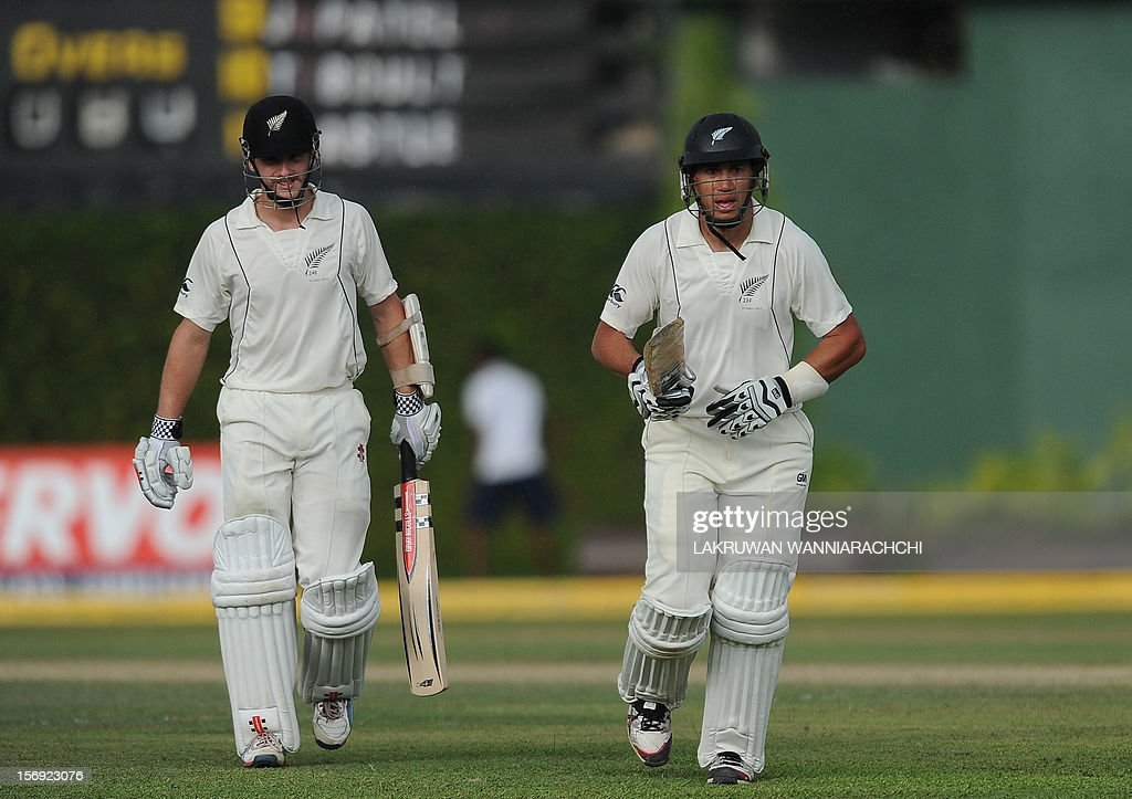 New Zealand captain Ross Taylor (R) and teammate Kane Williamson (L) leaves the pitch as rain stopped play during the first day of the second and final Test match between Sri Lanka and New Zealand at the P. Sara Oval Cricket Stadium in Colombo on November 25, 2012. AFP PHOTO/ LAKRUWAN WANNIARACHCI