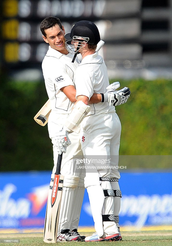New Zealand captain Ross Taylor (L) is congratulated by teammate Kane Williamson after scoring a century (100 runs) during the first day of the second and final Test match between Sri Lanka and New Zealand at the P. Sara Oval Cricket Stadium in Colombo on November 25, 2012. AFP PHOTO/ LAKRUWAN WANNIARACHCI