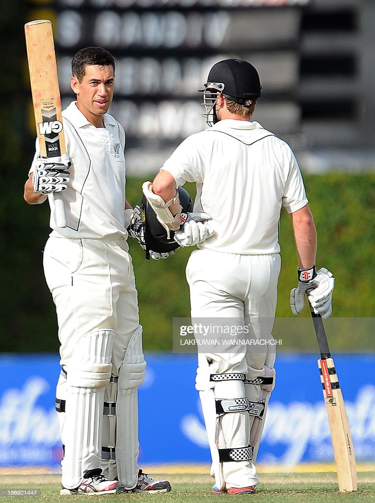 New Zealand captain Ross Taylor raises his bat and helmet in celebration after scoring a century (100 runs) as teammate Kane Williamson looks on during the first day of the second and final Test match between Sri Lanka and New Zealand at the P. Sara Oval Cricket Stadium in Colombo on November 25, 2012.