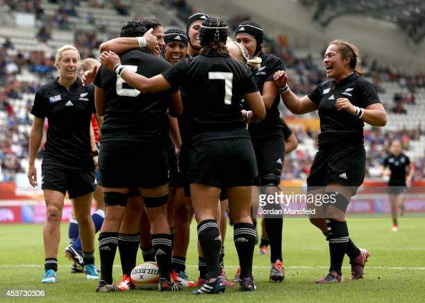 New Zealand celebrate with Aroha Savage after she scores a try during the IRB Women's Rugby World Cup 2014 5th/6th Place Playoff match between USA...