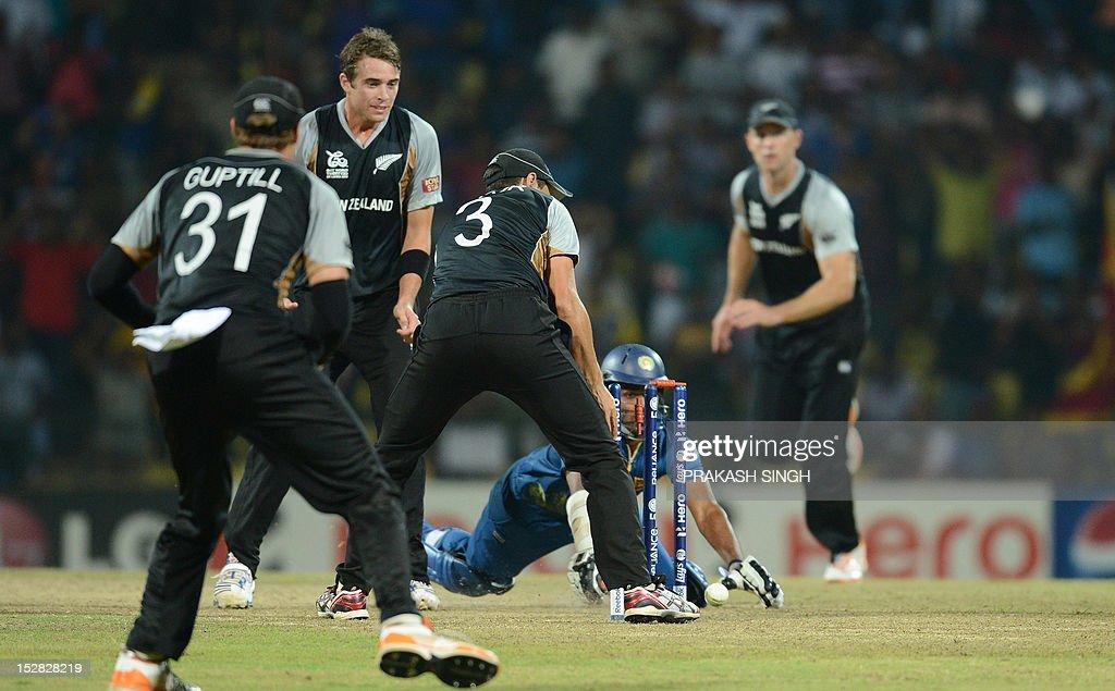 New Zealand cricket captain Ross Taylor (C, #3) successfully runs out Sri Lanka cricketer Lahiru Thirimanne (2R) during the ICC Twenty20 Cricket World Cup's Super Eight match between Sri Lanka and New Zealand at the Pallekele International Cricket Stadium in Pallekele on September 27, 2012. AFP PHOTO/ Prakash SINGH