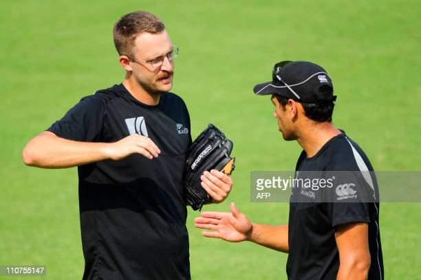 New Zealand cricket team captain Daniel Vettori speaks with teammate Ross Taylor during a training session at The Shere Bangla National Stadium in...