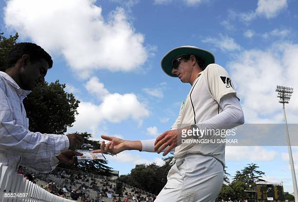 New Zealand cricketer Iain O'Brien signs autographs during the third day of the first Test match between India and New Zealand at the Seddon Park...