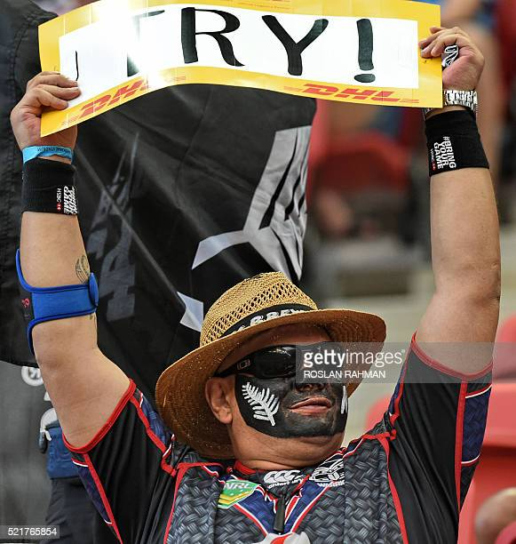 A New Zealand fan cheers for the team against South Africa during their Cup quarterfinal match at the Singapore Sevens rugby tournament on April 17...