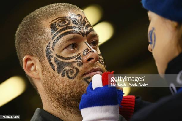New Zealand fan has his face painted by a rival France fan before the 2015 Rugby World Cup Quarter Final match between New Zealand and France at the...