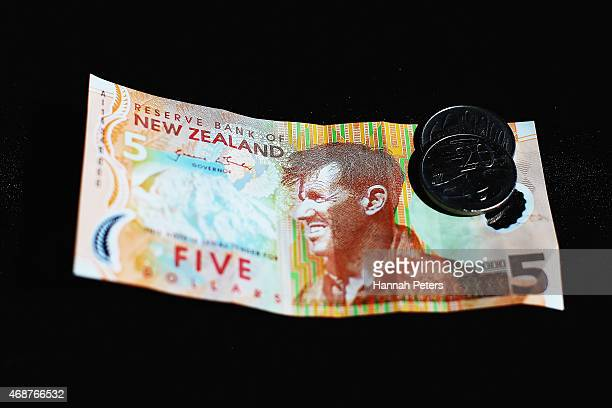 New Zealand five dollar banknote and Australian coins are arranged for a photo on April 7 2015 in Auckland New Zealand The New Zealand dollar could...