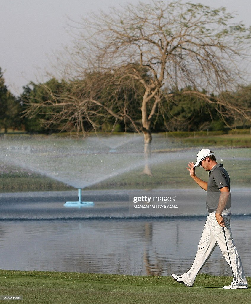 New Zealand golfer Mark Brown acknowledges the crowd's applause as he arrives to take a putt on the eighteenth hole during the Johnnie Walker Classic...
