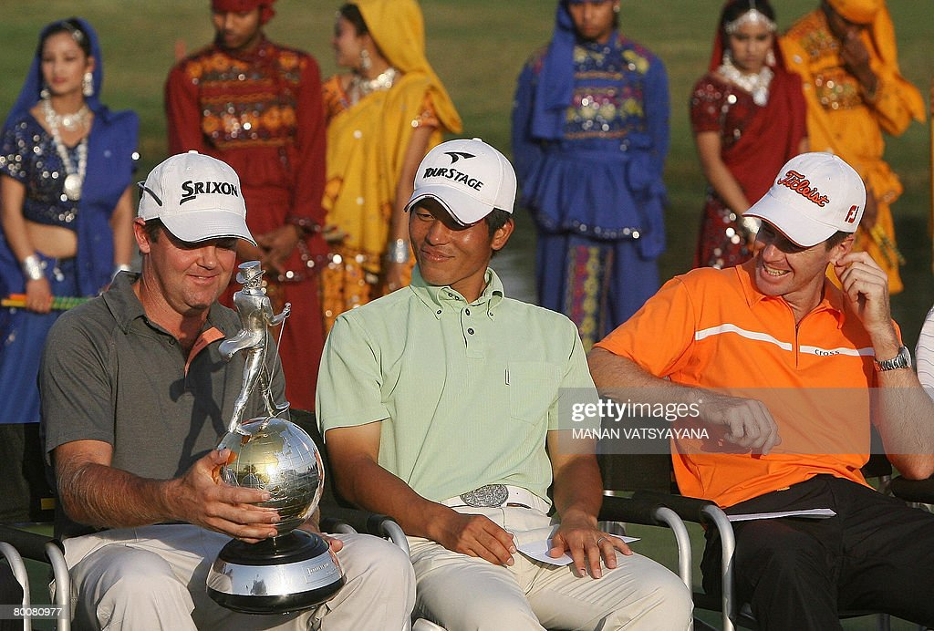 New Zealand golfer Mark Brown holds his winning trophy as runnersup Japanese Taichiro Kiyota and Australian Scott Strange look on at the Johnnie...
