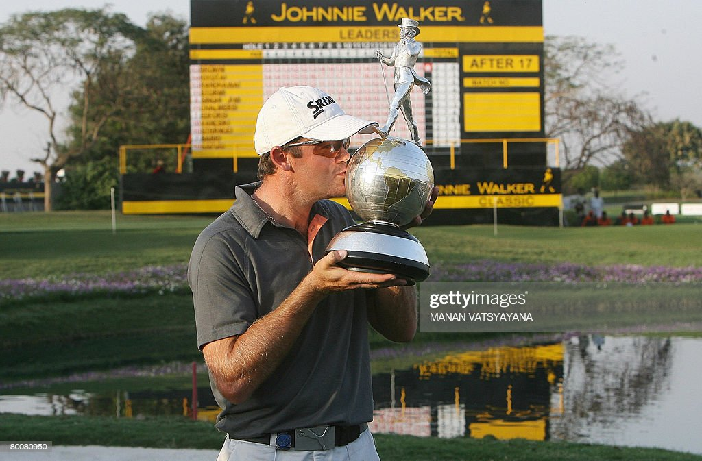new Zealand golfer Mark Brown kisses his trophy after winning the Johnnie Walker Classic 2008 in Gurgaon on the outskirts of New Delhi on March 2...