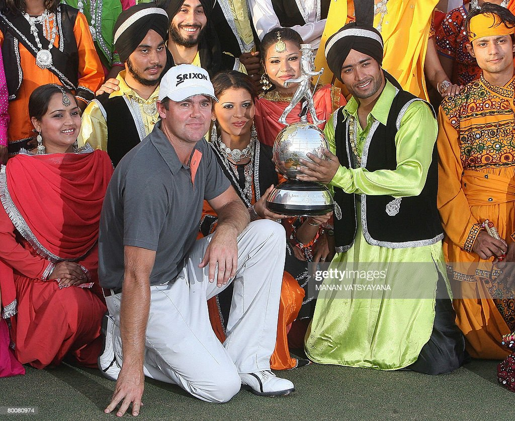 New Zealand golfer Mark Brown poses with his trophy along with Indian traditional dancers after winning the Johnnie Walker Classic 2008 in Gurgaon on...