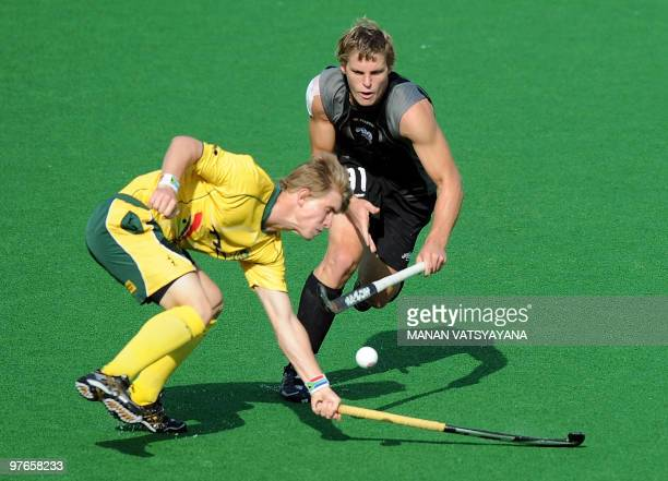 New Zealand hockey player Steve Edwards vies for the ball with South Africa's Taine Paton during their World Cup 2010 Classification match for 9th...
