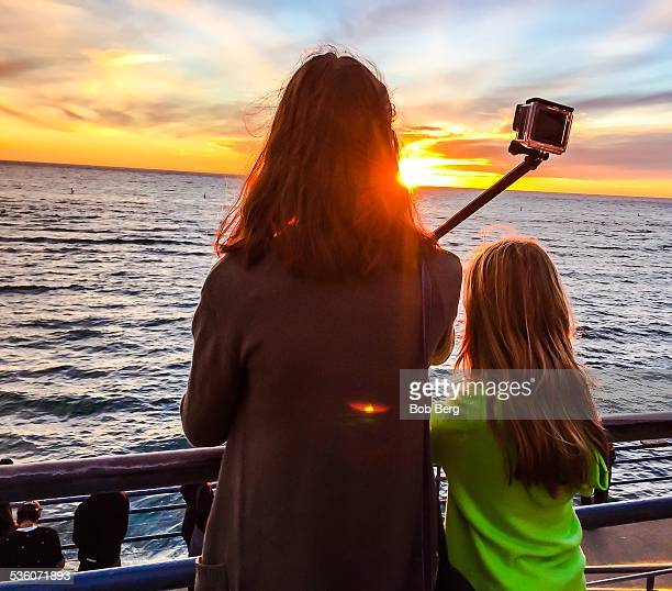 Santa Monica Ca January 22 2015 A New Zealand mother and daughter take a family selfie with a selfie stick at sunset on the Santa Monica pier