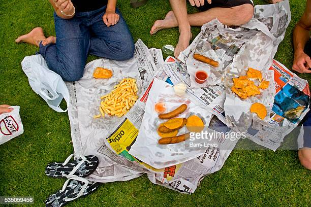New Zealand North Island Tauranga Bay of Plenty People eating Fish and chips on newspaper in the park