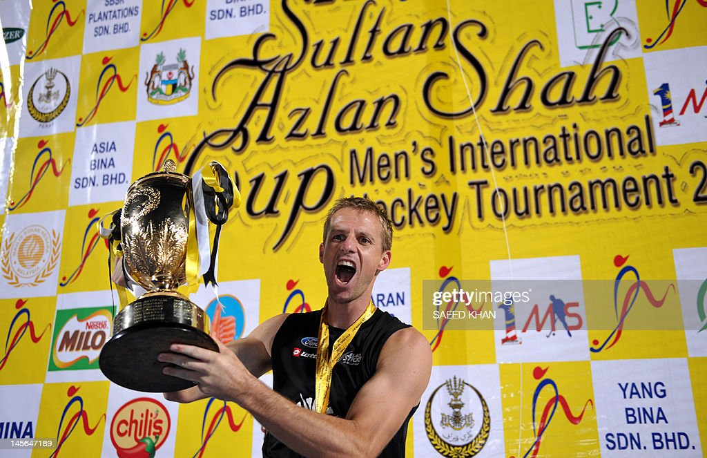 New Zealand player Dean Couzins shouts in jubilation with the trophy after defeating Argentina to win the Sultan Azlan Shah Cup men's field hockey...
