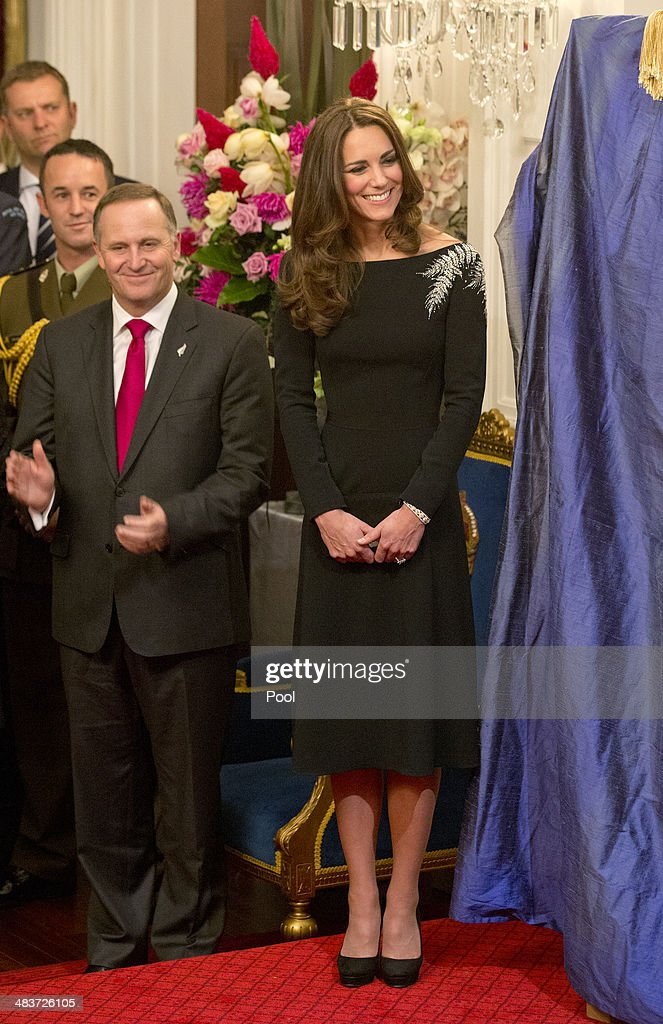New Zealand Prime Minister John Key and Catherine, Duchess of Cambridge look on as they attend an art unveiling of a portrait of Queen Elizabeth II by New Zealand artist Nick Cuthell during Day 4 of a Royal Tour to New Zealand at Government House on April 10, 2014 in Wellington, New Zealand. The Duke and Duchess of Cambridge are on a three-week tour of Australia and New Zealand, the first official trip overseas with their son, Prince George of Cambridge.