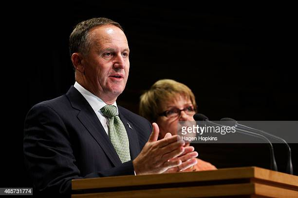 New Zealand Prime Minister John Key talks to the media while Food Safety Minister Jo Goodhew looks on at Parliament House on March 10 2015 in...