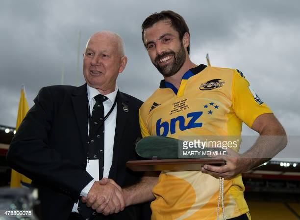 New Zealand Rugby Union board president Ian MacRae presents a Mere to Wellington Hurricanes captain Conrad Smith for his 100th Super Rugby game...