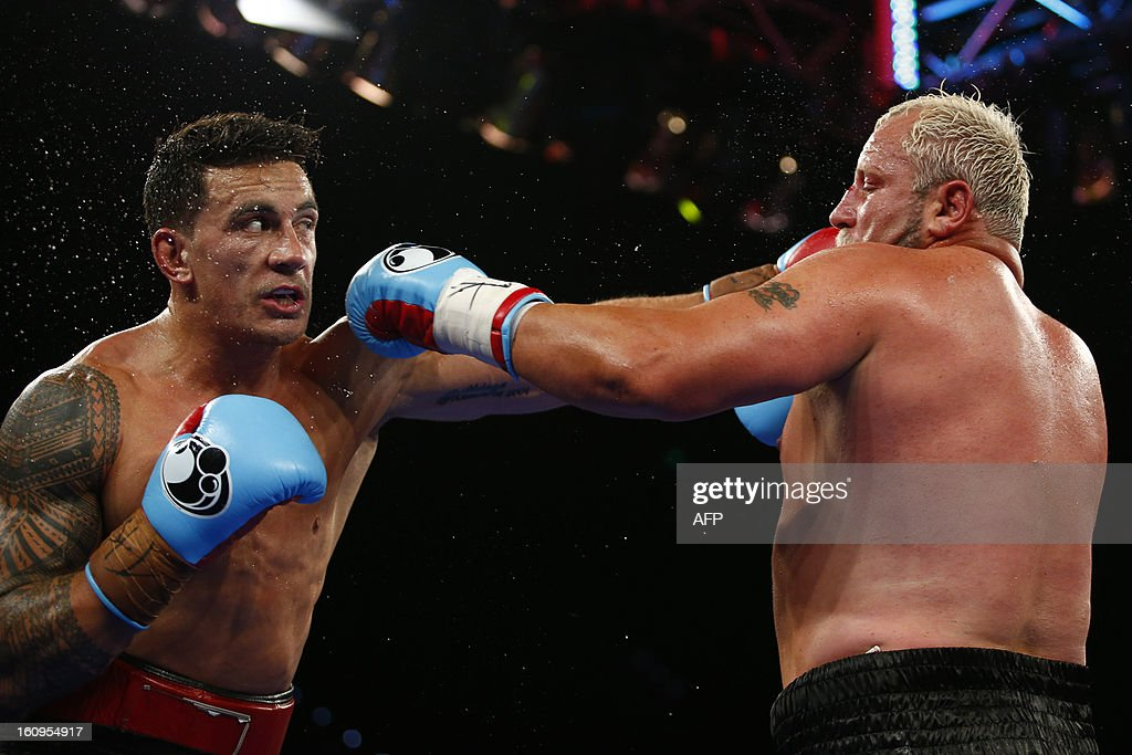 New Zealand rugby union player Sonny Bill Williams (L) lands a punch on Francois Botha of South Africa during their WBA International Heavyweight Title fight at the Brisbane Entertainment Centre on February 8, 2013. AFP PHOTO / Patrick HAMILTON AFP PHOTO / Patrick HAMILTON USE