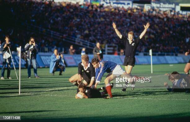 New Zealand scrumhalf David Kirk passes France's Patrice Lagisquet to score a try during the Rugby Union World Cup Final in Auckland 20th June 1987...