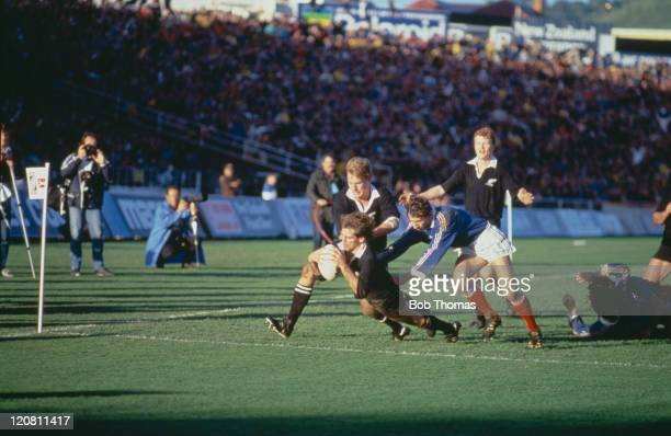 New Zealand scrumhalf David Kirk scores a try in the corner with the help of teammate John Kirwan during the Rugby Union World Cup Final against...