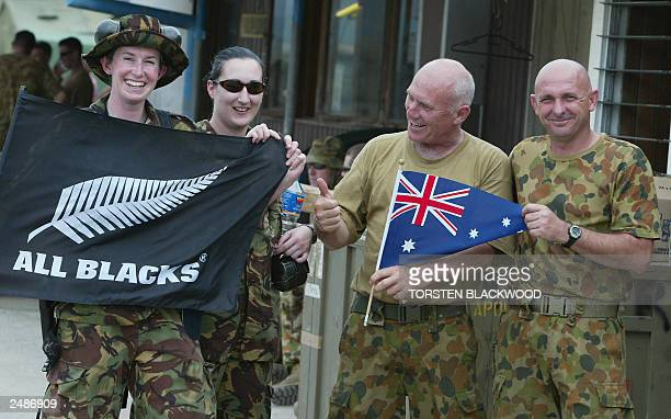 New Zealand soldiers Michelle White and Karina Henderson show the silver fern flag while Australian soldiers Ray Costello and Dave Kay show their...