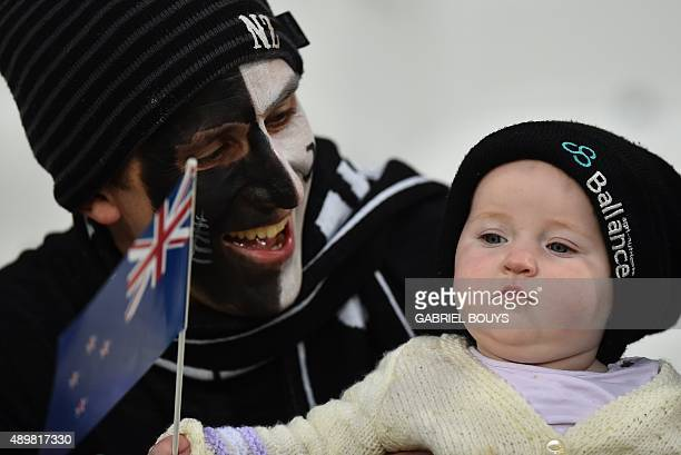 A New Zealand supporter poses with a baby prior to a Pool D match of the 2015 Rugby World Cup between New Zealand and Namibia at the Olympic stadium...