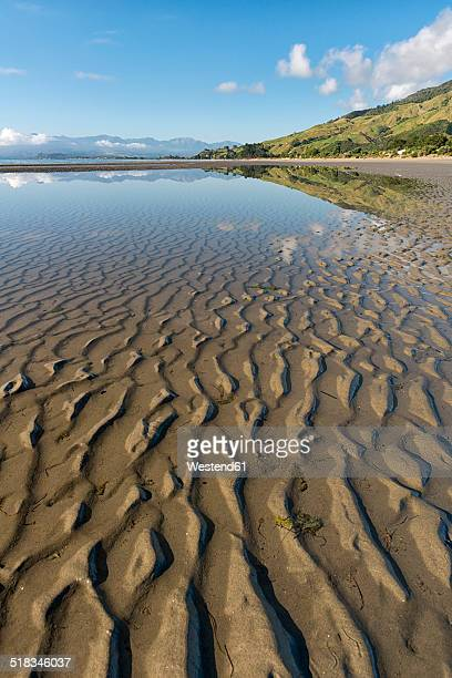 New Zealand, Tasman, Golden Bay, Pakawau, reflections of clouds in the water and structures in the sand at low tide