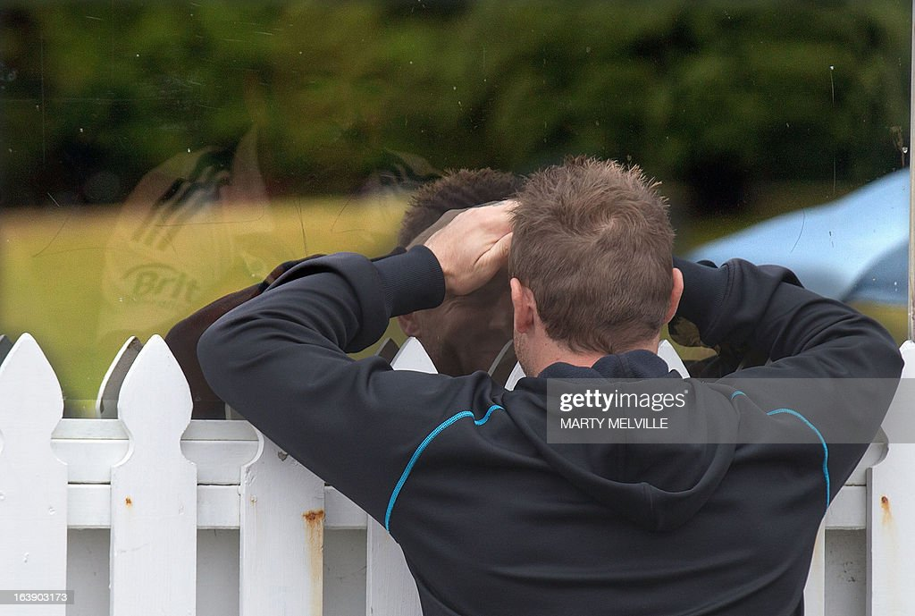 New Zealand team team captain Brendon McCullum (R) speaks to England's Matt Prior through a window as rain halts play during day five of the international cricket Test match between New Zealand and England played at the Basin Reserve in Wellington on March 18, 2013. AFP PHOTO / Marty MELVILLE