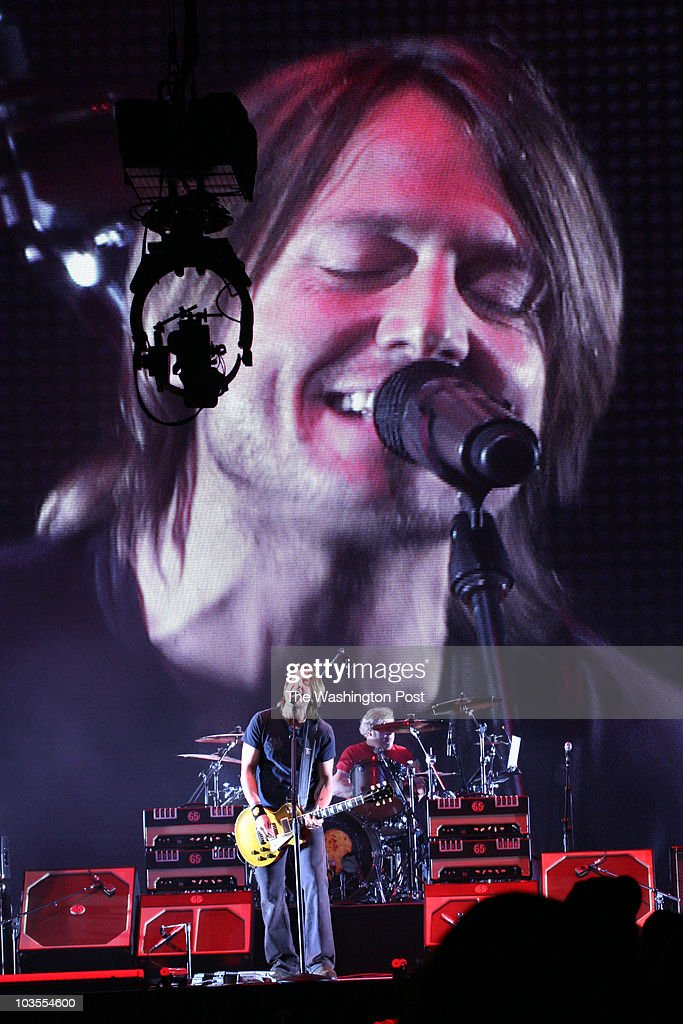 New Zealand-born country music singer and songwriter Keith Urban performing at the MCI Center. A huge tv screen projected his image in background as he performed, here with drummer.