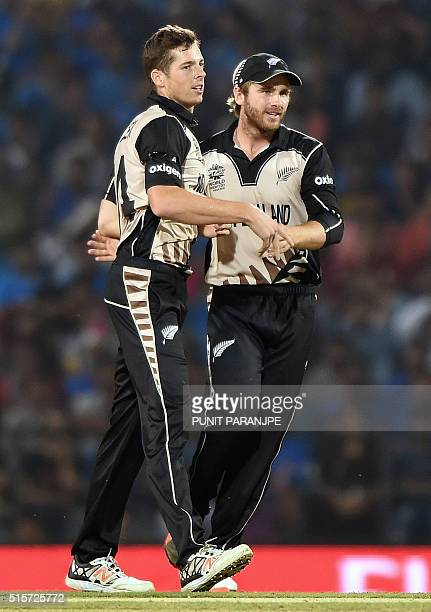 New Zealander bowler Mitchell Santner celebrates with captain Kane Williamson after the wicket of India's batsman Hardik Pandya during the World T20...