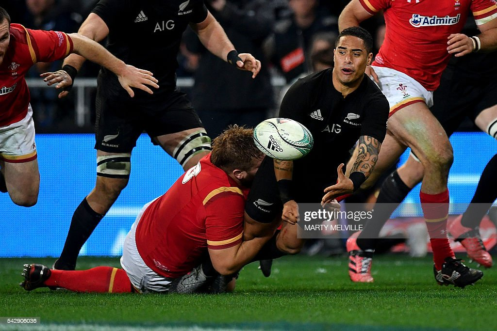 New Zealand's Aaron Smith (R) gets a pass away as he is tackled by Tomas Francis of Wales (bottom L) during the third rugby union Test match between the New Zealand All Blacks and Wales at Forsyth Barr Stadium in Dunedin on June 25, 2016. / AFP / Marty Melville