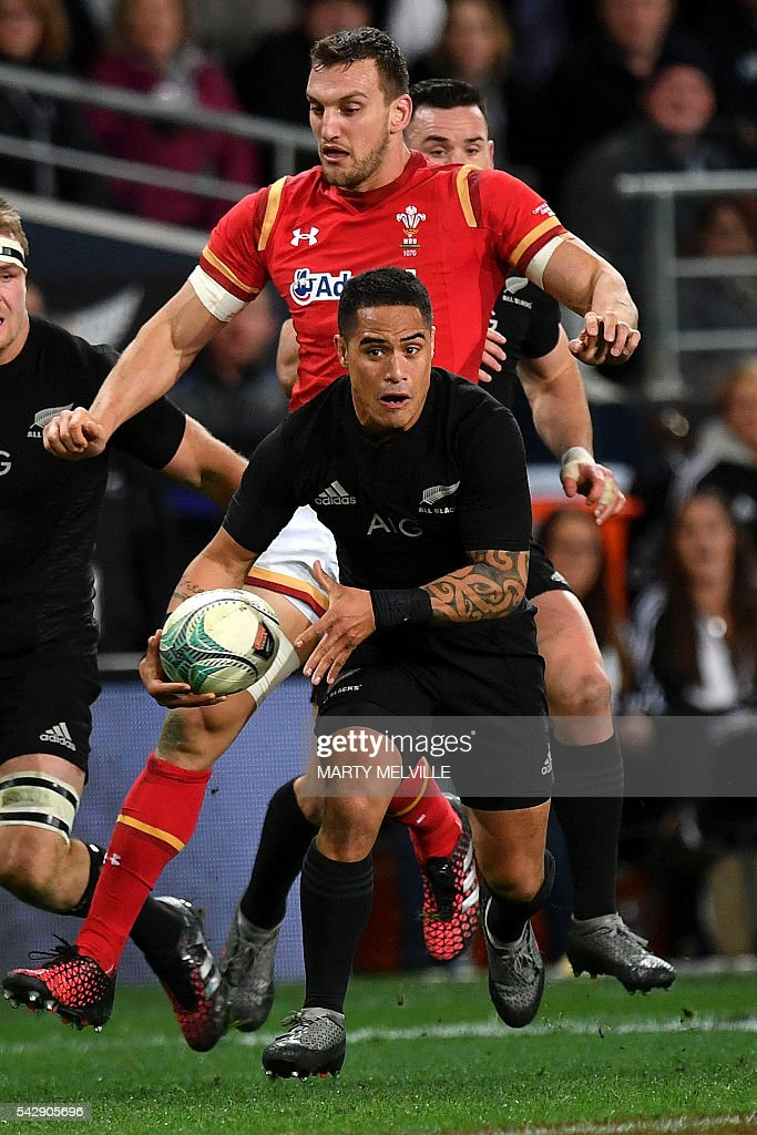 New Zealand's Aaron Smith (C) runs with the ball as Sam Warburton of Wales (behind) gives chase during the third rugby union Test match between the New Zealand All Blacks and Wales at Forsyth Barr Stadium in Dunedin on June 25, 2016. / AFP / Marty Melville