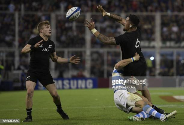 New Zealand's All Blacks flanker Vaea Fifita passes the ball to teammate Damian McKenzie while being takled by Argentina's Los Pumas wing Emiliano...