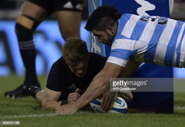 New Zealand's All Blacks fullback Damian McKenzie scores the team's second try next to Argentina's Los Pumas prop Nahuel Tetaz Chaparro during their...