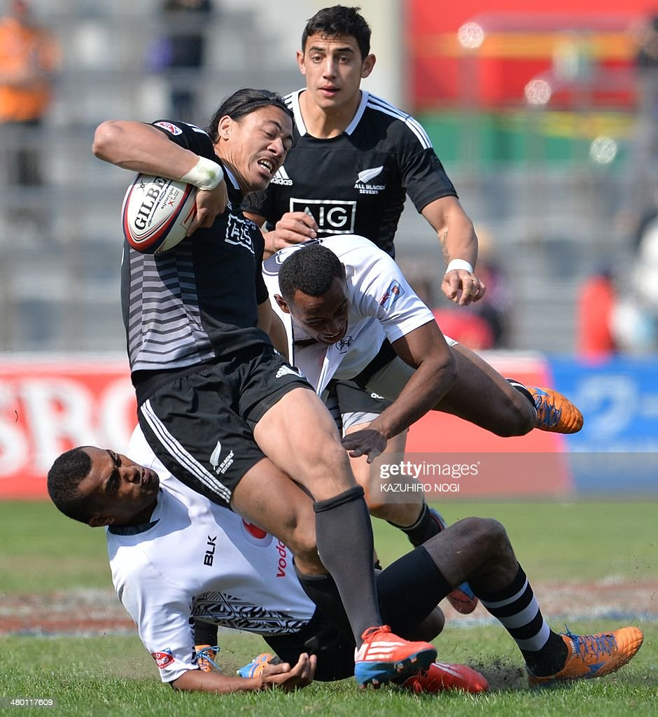 New Zealand's Ben Lam (C) is tackled by Fiji's players Donasio Ratubuli Naturaga (R) and Samisoni Viriviri (L, bottom) during their Tokyo Sevens 2014 Cup semi-final match, part of the Rugby Sevens World Series, in Tokyo on March 23, 2014. Fiji won the match. AFP PHOTO / KAZUHIRO NOGI