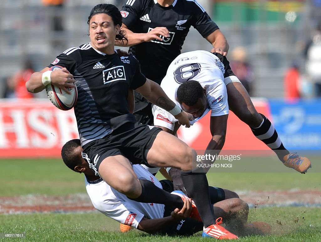 New Zealand's Ben Lam (C) is tackled by Fiji's players Donasio Ratubuli Naturaga (R) and Samisoni Viriviri (L, bottom) during their Tokyo Sevens 2014 Cup semi-final match, part of the Rugby Sevens World Series, in Tokyo on March 23, 2014. Fiji won the match.