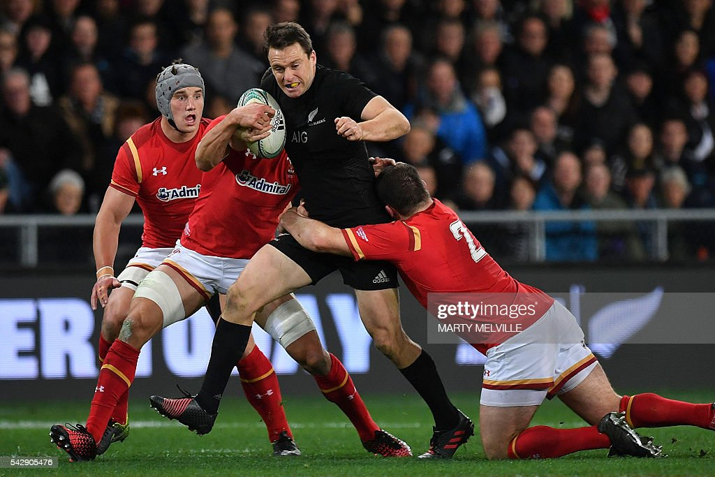New Zealand's Ben Smith (C) is tackled by Sam Warburton (2nd L) and Ken Owens (R) of Wales during the third rugby union Test match between the New Zealand All Blacks and Wales at Forsyth Barr Stadium in Dunedin on June 25, 2016. / AFP / Marty Melville