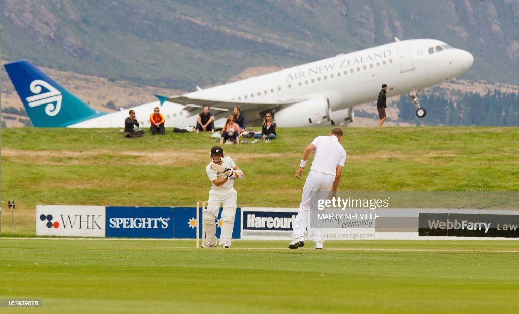 New Zealand's BJ Watling (front L) bats as an Air New Zealand plane takes off on the last day of the four day warm-up international cricket match between New Zealand XI and England in Queenstown on March 2, 2013. AFP PHOTO / Marty MELVILLE