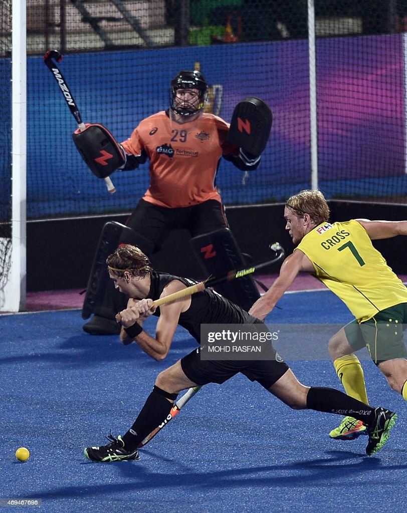 New Zealand's Blair Hilton hits the ball as Australia goalkeeper Leon Hayward looks on during the Sultan Azlan Shah Cup men's field hockey tournament...
