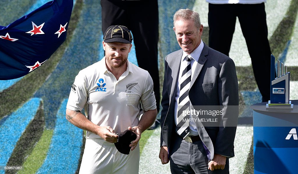 New Zealand's Brendon McCullum (L) receives a cap for 100 test matches from Stephen Boock chairman of New Zealand cricket during day one of the first cricket international five-day Test match between New Zealand and Australia at Basin Reserve in Wellington on February 12, 2016. / AFP / Marty Melville