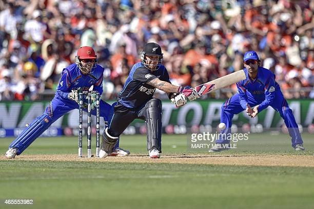 New Zealand's captain Brendon McCullum plays a shot watched by Afghanistan's keeper Afsar Zazaid and Asghar Stanikzai during the Pool A 2015 Cricket...