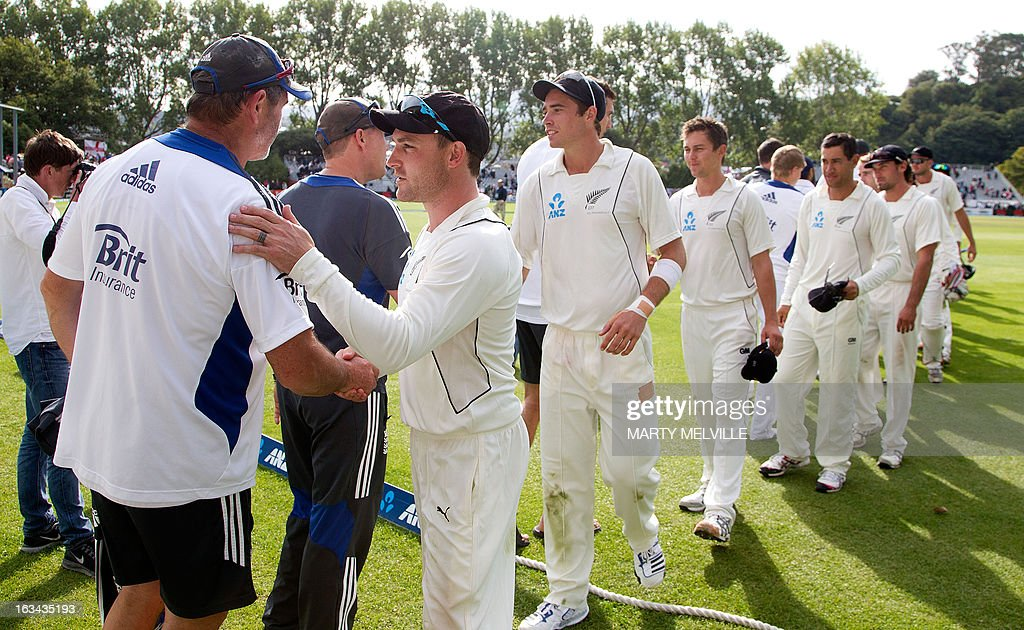 New Zealand's captain Brendon McCullum (R) shakes hands with England's batting coach Graham Gooch at the end of play during day four of the first international cricket Test match between New Zealand and England played at the University Oval park in Dunedin on March 10, 2013. AFP PHOTO / Marty MELVILLE