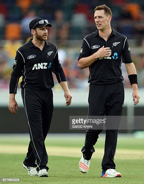 New Zealand's captain Kane Williamson talks to paceman Matt Henry as he prepares to bowl Australia's batsman Mitchell Marsh during the second game of...