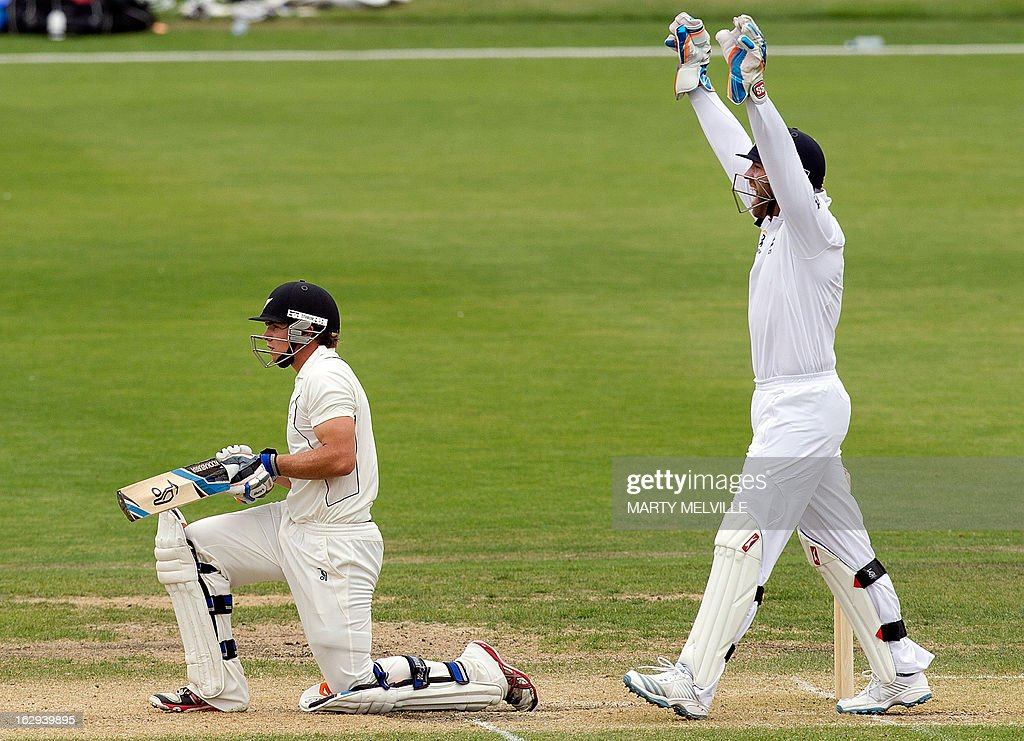 New Zealand's captain Tom Latham (L) kneels as England's Matt Prior celebrates catching him out on the last day of the four day warm-up international cricket match between New Zealand XI and England in Queenstown on March 2, 2013. AFP PHOTO / Marty MELVILLE