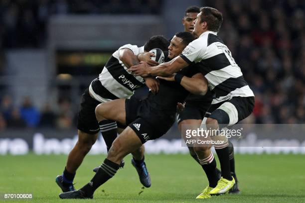 New Zealand's centre Ngani Laumape is tackled by Barbarians' New Zealand wing Vince Aso and Barbarians' South African centre Harold Vorster during...
