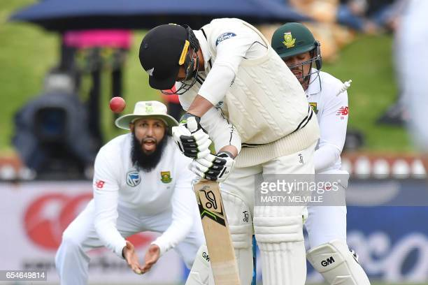 New Zealand's Colin De Grandhomme is bowled watched by South Africans Hashim Amla and Quinton de Kock during day three of the second Test cricket...