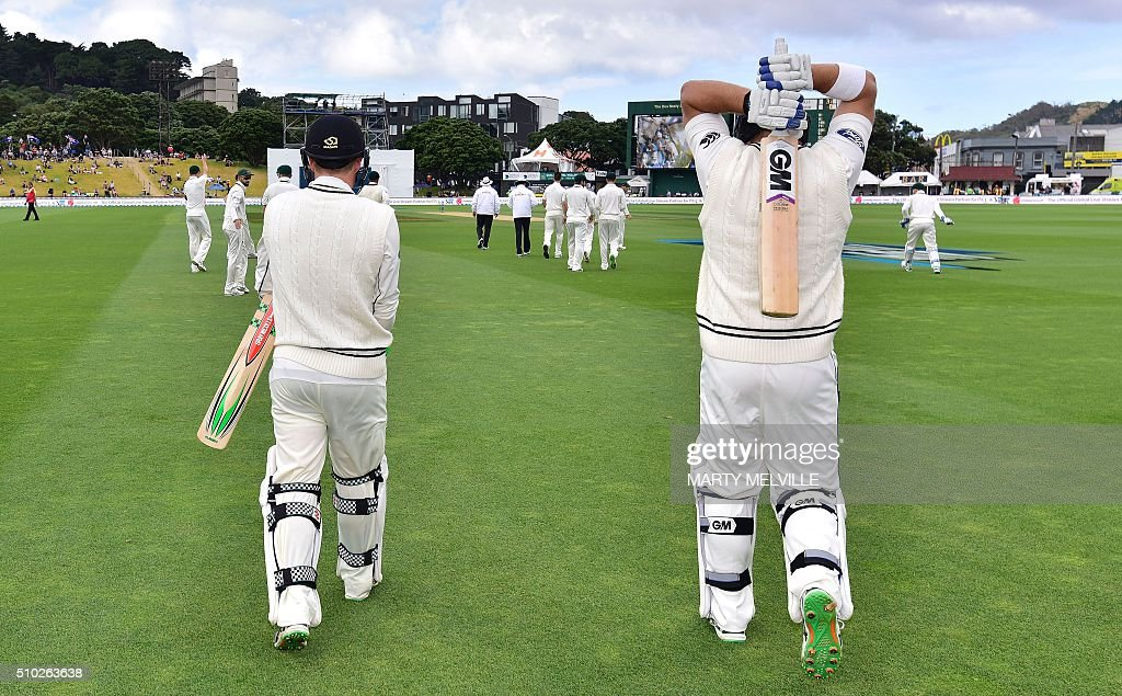 New Zealand's Corey Anderson (R with team mate Henry Nicholls walk out onto the field at the start of the days play during day four of the first cricket Test match between New Zealand and Australia at the Basin Reserve in Wellington on February 15, 2016. / AFP / Marty Melville